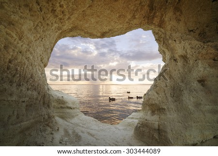 fiery sunset from inside a cave that creates a frame in the shape of heart