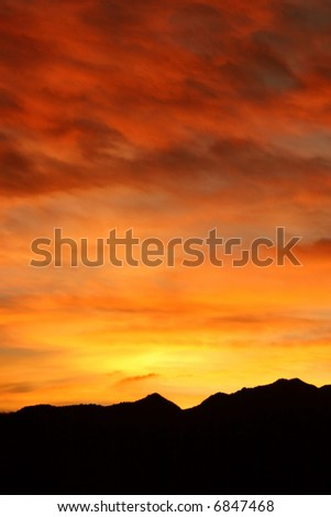 Fiery winter sunrise in the Colorado Rocky Mountains boasts brilliant shades of red, orange, and yellow. - stock photo