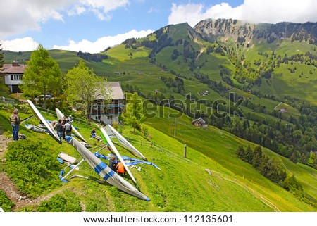 FIESH, SWITZERLAND - JULY 2: Competitors are taking part in the Fiesh Open hang gliding competitions takes part on July 2, 2012 in Fiesh, Switzerland - stock photo