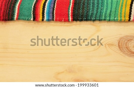 fiesta Mexican poncho rug in bright colors with wooden background - stock photo