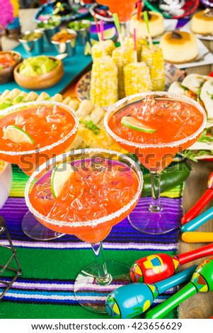 Fiesta party buffet table with watermelon margaritas and other traditional Mexican food.