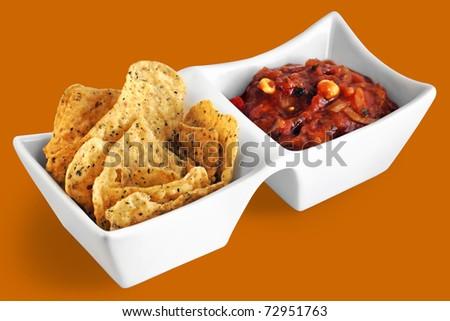 Fiesta: Tortillas chips and salsa in white serving dish on fun orange background. - stock photo