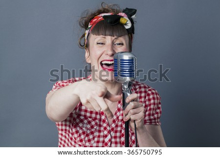 fifties singer in studio - performing 30s female rocker and vocal artist with retro style singing in old fashioned micro with fingers pointing to camera, gray background - stock photo