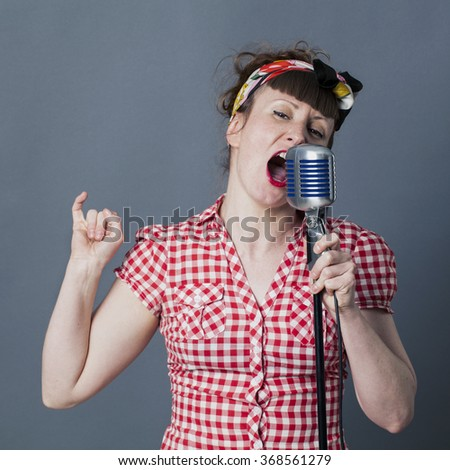 fifties singer in studio - shouting young female rocker and vocal artist with retro style singing in old fashioned microphone, gray background