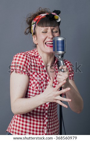 fifties singer in studio - singing young woman with retro style performing with old fashioned micro, gray background