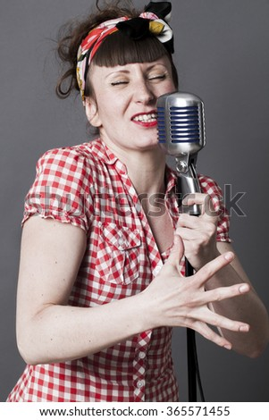 fifties singer in studio - young woman with retro style singing in old fashioned microphone, gray background - stock photo