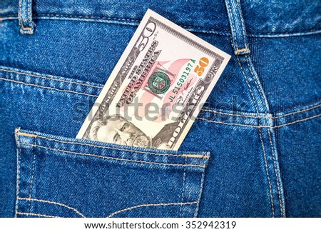 Fifty american dollars bill sticking out of the back jeans pocket - stock photo