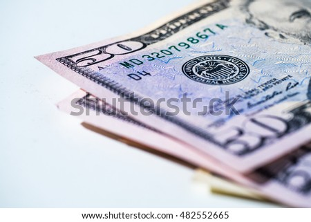Fifty dollar bills laying out on a white background - money, finance imagery