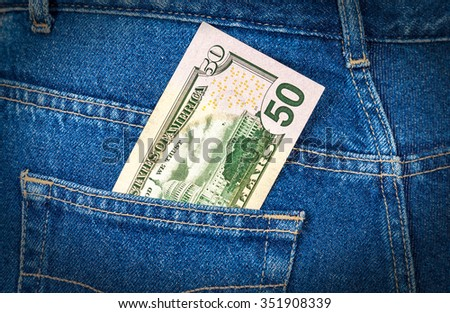 Fifty dollars bill sticking out of the blue jeans pocket