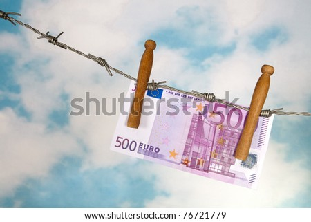 Fifty euro banknote hanging on barbed wire - stock photo