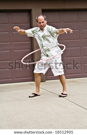 Fifty-five year old man plays with a hula hoop. - stock photo