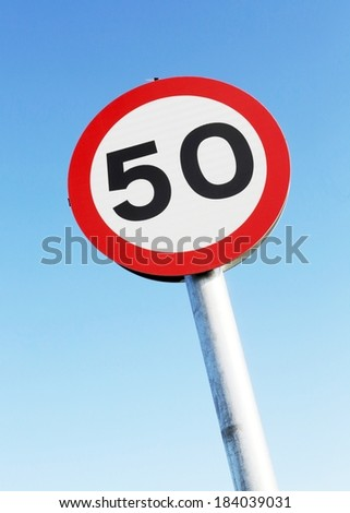Fifty miles per hour speed limit sign against a clear blue sky.  - stock photo