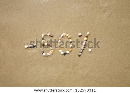 fifty percent discount word writing with small stones on sand beach ground - stock photo