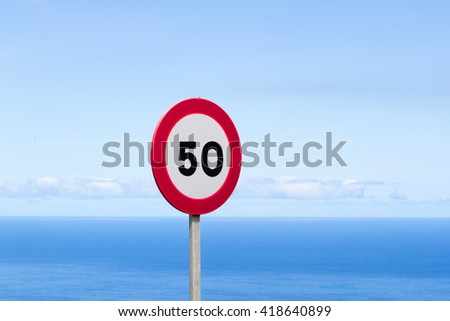 Fifty traffic sign. 50 miles per hour speed limit sign round red against blue sky
