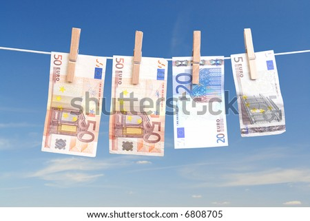 Fifty, twenty and five euro banknotes hanging on laundry line attached with wooden clips over blue sky - stock photo