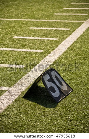 Fifty Yard Line Marker On Sidelines Of Football Field - stock photo