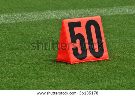 Fifty yard line marker on the side of football field - stock photo