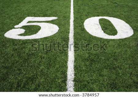 Fifty yard line on a perfectly manicured American Football field. - stock photo