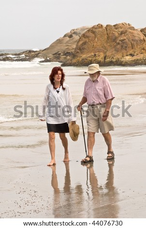 Fifty year old woman and senior man walking on beach - stock photo