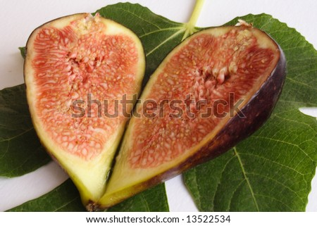 Fig halves on a leave on white background - stock photo