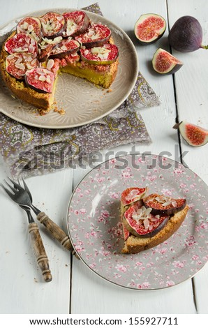Fig homemade tart with almonds on old wood table