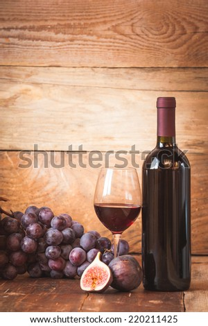 Fig with red wine, grape and barrel on rustic wood table - stock photo