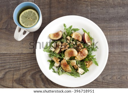 Fig with rucola, a summer mediterranean dish with lemon tea in a mug.
