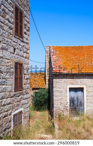 Figari, South Corsica. Rural architecture example. Old houses made of stones with red tile roofs, wooden doors and windows - stock photo