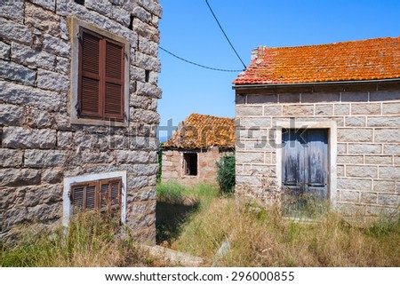 Figari, South Corsica, rural architecture example. Old living houses made of stones with red tile roofs, wooden doors and windows - stock photo