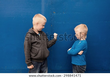 fight between two brothers (kids, boys), angry aggressive children - stock photo