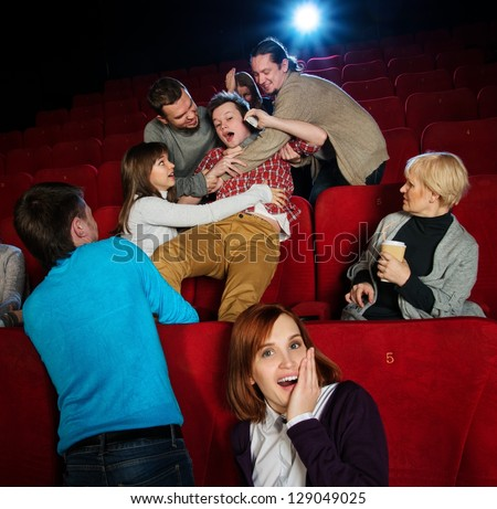 Fight between young men happening in cinema during film show - stock photo