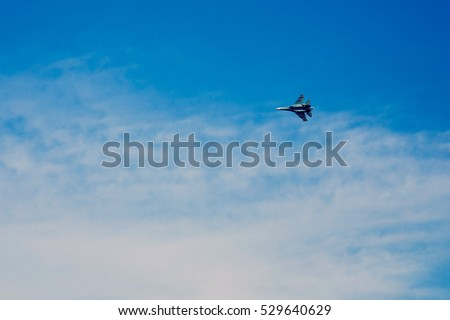 Fighter Plane flying in the blue sky with clouds