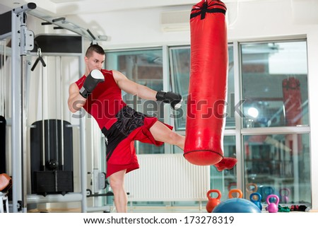 Fighter practicing some kicks with a punching bag at a gym - stock photo