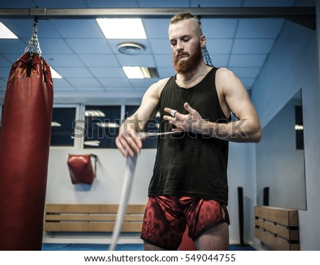 Fighter preparing for training, wrapping hands with boxing wraps