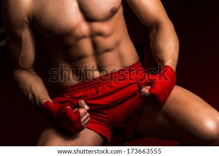 Fighter Putting Straps On His Hands - Muscled Boxer Wearing Red Strap On Wrist