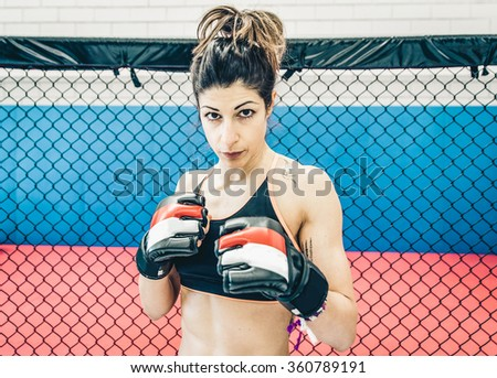 Fighter woman portrait in the mma cage. Concept about fighting and mixed martial arts - stock photo