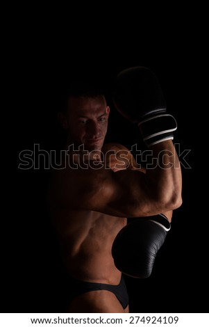 Fighter. Young sexy muscular shirtless man with boxing gloves looking into camera isolated on black background. Sport and fitness.   - stock photo