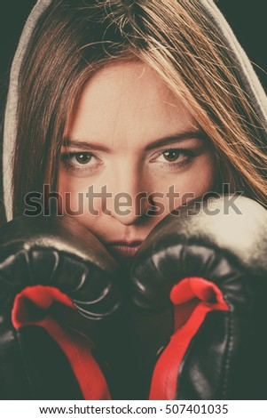 Fighting boxing and defense. Sportsmanship and strong body. Young woman wear sportswear and boxing gloves cover face look at opponent.
