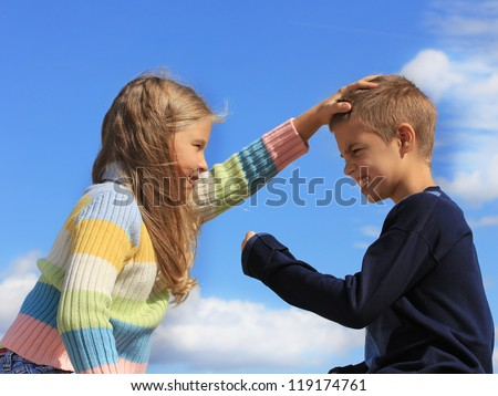 Fighting brother and the sister against a blue sky - stock photo