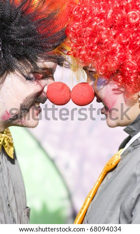Fighting Clowns Battle It Out Face To Face And Nose To Nose In A Humorous Funny Fight - stock photo