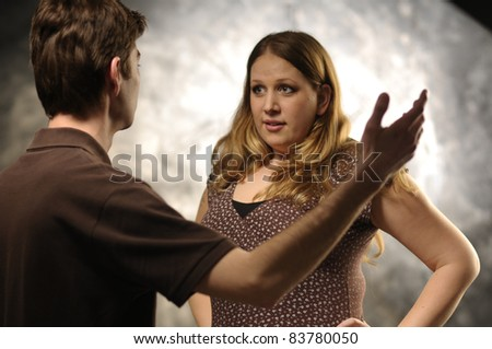 Fighting couple on gray background - stock photo