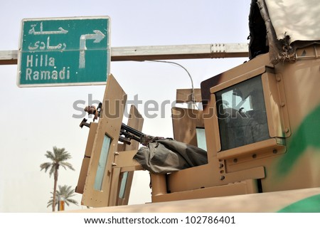 Fighting in Iraq. An armored vehicle in position next to a road leading to Hilla and Ramadi in central Iraq. A closeup showing the machine gun turret. - stock photo