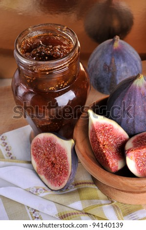 Figs and jar with fig jam on background