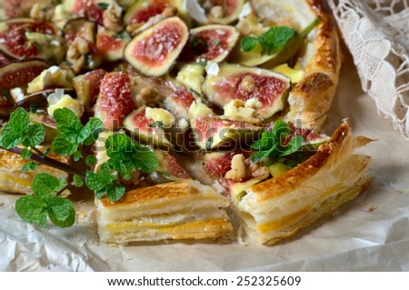 Figs, camembert, walnuts and honey puff tart. Selective focus
