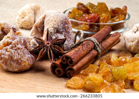 figs, cinnamon, anise and raisins on wooden tray, selective focus - stock photo