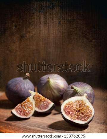 Figs on wooden board with textured rustic background