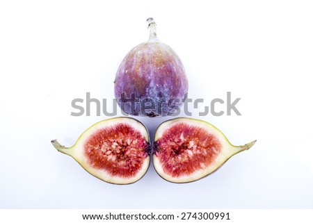 Figs whole and halved shot on white background arranged in triangle - stock photo