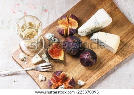Figs with blue cheese, white wine and crackers on wooden cutting board. Top view.  - stock photo
