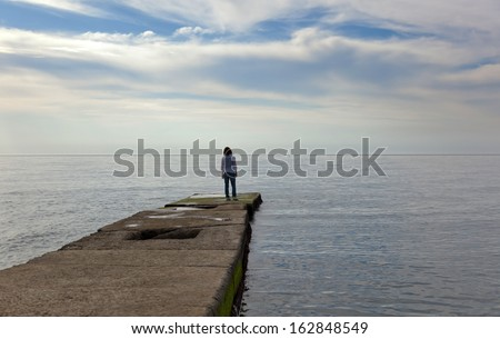 figure of a girl on a pier on the background of sky and sea - stock photo