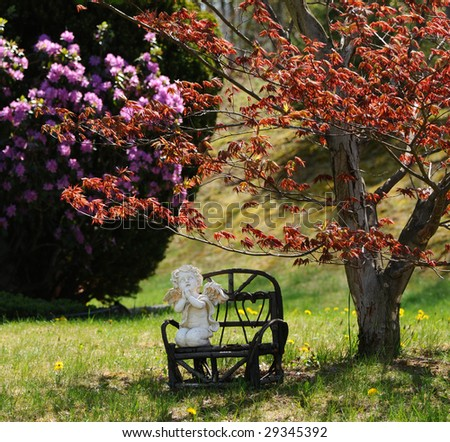 Figure of a praying cupid on  a wooden bench in spring.